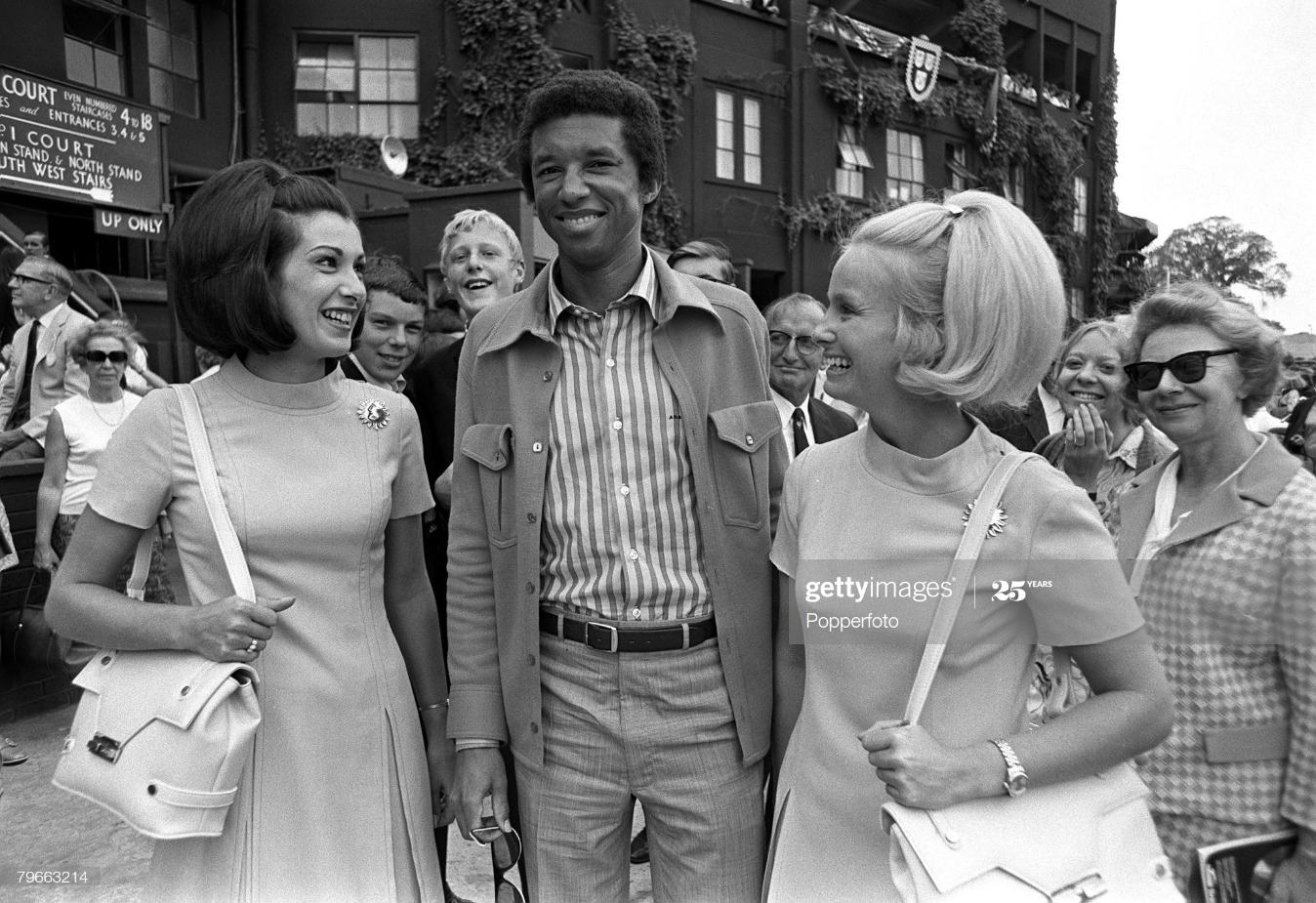 Sport, Tennis, All England Lawn Tennis Championships, Wimbledon, England, 26th June 1970, Mens Singles, USA's Arthur Ashe is greeted at Wimbledon by two attractive female American fans, prior to the start of the Championships : News Photo